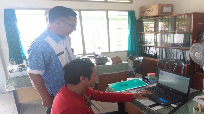 Kepsek SMPN 5 Bintan, Elnui tengah memantau PPDB di sekolahnya. Foto diambil beberapa waktu lalu sebelum pandemi covid-19.