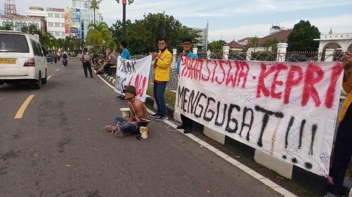 AKSI TUTUP MULUT - Beberapa laki-laki menutup mulutnya dengan lakban saat melakukan aksi tolak UU Cipta Kerja di seberang Gedung Daerah Tanjungpinang, Rabu (28/10/2020)