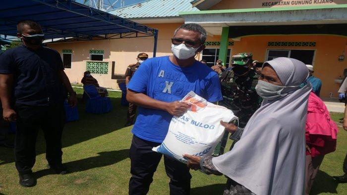 Bupati Bintan, Apri Sujadi menyerahkan bantuan beras PPKM seberat 10 Kilogram kepada warga Desa Malang Rapat Bintan, Kamis (29/7/2021)