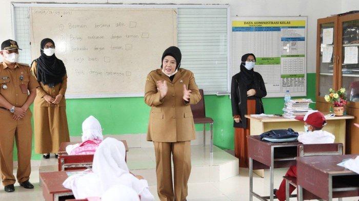 MARLIN AGUSTINA - Wakil Gubernur Kepri, Hj. Marlin Agustina berdiri dengan seorang anak sekolah dasar saat berkunjung ke SD Negeri 007 Kapling Lama Subgai Daun, Tanjungpiayu, beberapa hari lalu.
