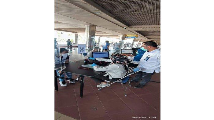 APLIKASI - Calon penumpang sedang menggunakan aplikasi PeduliLindungi melalui handphone saat hendak berangkat melalui Bandara Hang Nadim Batam, Selasa (31/8/2021) siang.
