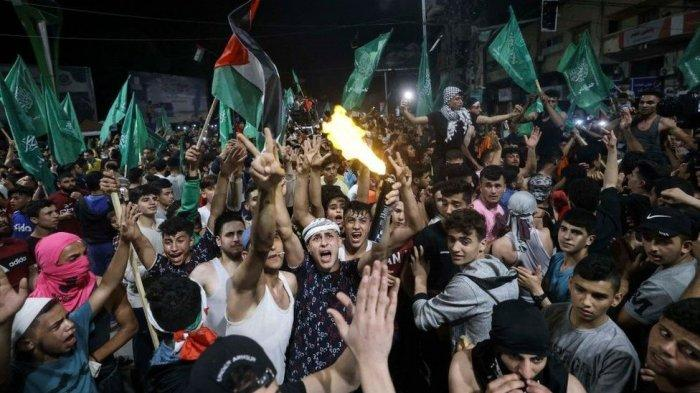 GENCATAN SENJATA - Setelah 11 hari Israel memborbardi pemukiman di Gaza, gencatan senjata ini akhirnya diumumkan untuk pertama kalinya. FOTO: WARGA GAZA RAYAKAN GENCATAN SENJATA