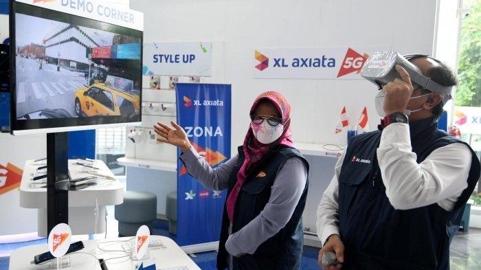 Presiden Direktur & CEO XL Axiata, Dian Siswarini (kiri) bersama dengan Direktur & Chief Technology Officer XL Axiata, I Gede Darmayusa (kanan) mencoba demo layanan 5G yang tersedia di XL Center, XL Axiata Tower, Jakarta