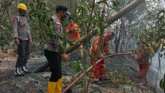 Personel Polsek Tanjungpinang Timur bersama petugas pemadam kebakaran saat sedang berusaha memadamkan lahan yang terbakar di Jalan Hanjoyo Putro, Kampung Sumber Karya, Kelurahan Batu IX, Tanjungpinang Timur, Minggu (21/2/2021) sore.