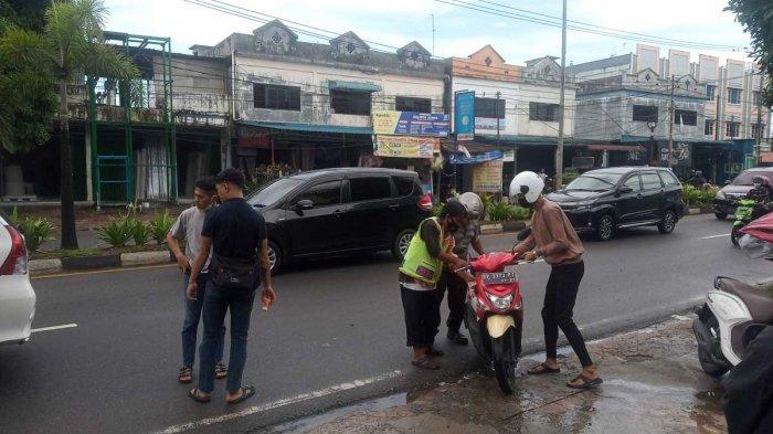 KECELAKAAN DI TANJUNGPINANG - Kondisi pengendara motor matik yang terpeleset dan menghantam belakang mobil saat dibantu warga sekitar, Kamis (3/6/2021).