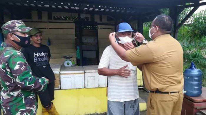 Lurah Daik Lingga, Aryanto bersama Babinsa membagikan masker kepada warganya yang menjalani isolasi mandiri akibat covid-19, Senin (9/8).