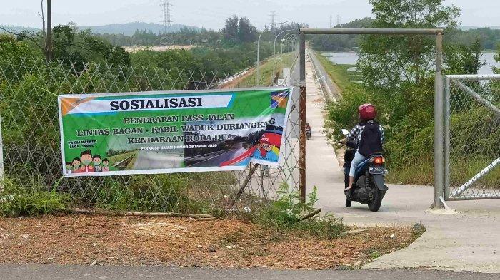 Pengendara roda dua saat akan keluar pintu lintas Waduk Duriangkang Bagan - Kabil, Senin (1/2/2021).