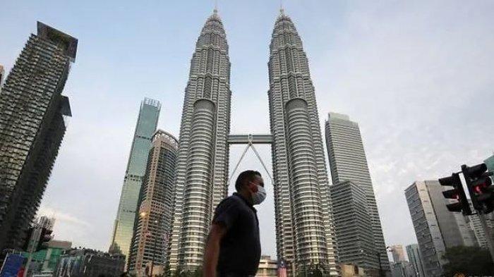 Seorang pria tampak mengenakan masker melintasi jalan di depan Menara Kembar Petronas di Kuala Lumpur, Malaysia, (11/8/2020).