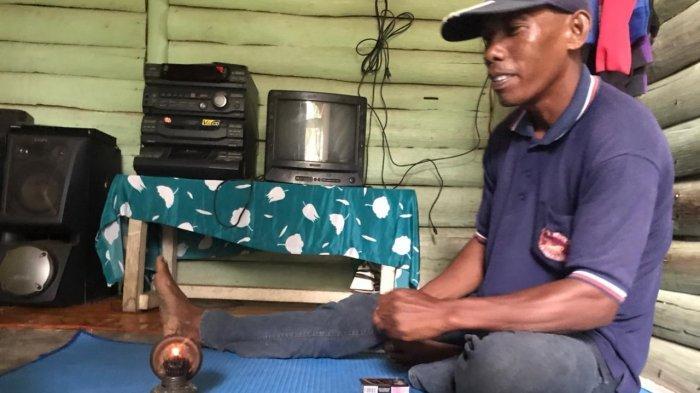 Warga Kampung Wono Sari, Wito saat menyalakan lampu pelita yang digunakan sehari-hari di rumahnya. Ia bersama sejumlah warga lainnya begitu menginginkan listrik PLN masuk rumah mereka.