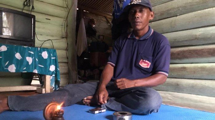 Warga Kampung Wono Asri, Wito saat menyalakan lampu pelita yang digunakan sehari-hari di rumahnya. Ia bersama sejumlah warga lainnya begitu menginginkan listrik PLN masuk rumah mereka.