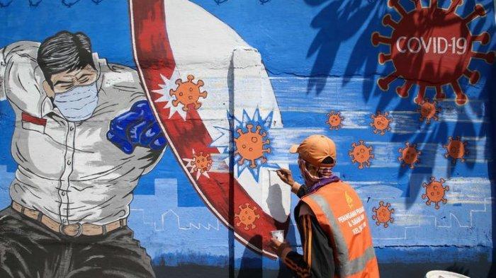 Gunawan, Petugas Penanganan Prasarana Sarana Umum (PPSU) Kelurahan Bukit Duri membuat mural bertemakan Covid-19 di kawasan Bukit Duri, Jakarta Selatan, Jumat (28/8/2020).