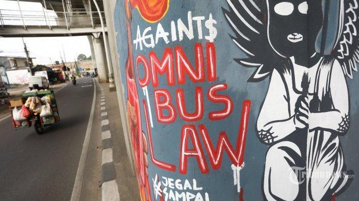 Pengendara melintas di dekat mural tentang UU Cipta Kerja di kawasan Pesanggrahan, Jakarta,. Rabu (14/10/2020). Mural tersebut sebagai kritik pemerintah beserta DPR terkait pengesahan UU Cipta Kerja.