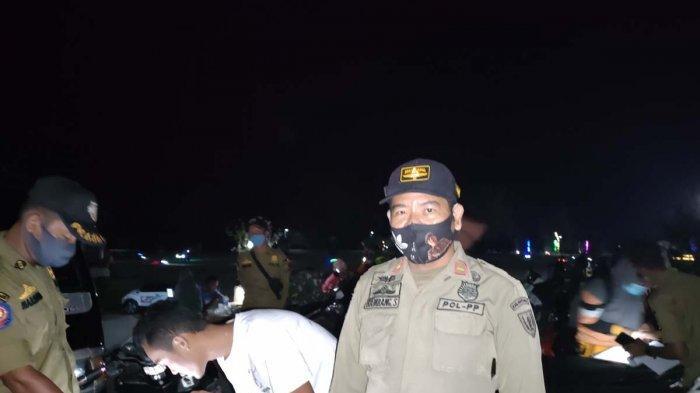 Personel Satpol PP Natuna Bambang Suryadi S.A.P saat operasi yustisi protokol kesehatan di Pantai Piwang, Kecamatan Bunguran Timur, Sabtu (3/4/2021) malam.
