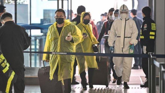 Orang-orang mengenakan pakaian pelindung diri melintas di Bandara Tianhe yang baru dibuka kembali di Wuhan, Hubei, China, Rabu (8/4/2020).
