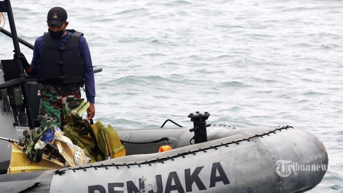 Prajurit TNI mengevakuasi serpihan dari pesawat Sriwijaya Air SJ 182 yang hilang kontak saat melakukan pencairan di perairan Kepulauan Seribu, Jakarta, Minggu (10/1/2021). Pesawat Sriwijaya Air SJ 182 yang hilang kontak pada Sabtu (9/1/2021) sekitar pukul 14.40 WIB di ketinggian 10 ribu kaki tersebut membawa enam awak dan 56 penumpang. TRIBUNNEWS/IRWAN