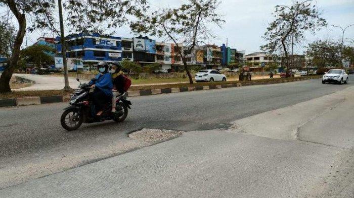 Pengendara roda dua tampak menurunkan laju kendaraan dan menghindari jalan bergelombang di Jalan Laksamana Bintan, dekat Simpang Patung Kuda, Minggu (21/2)