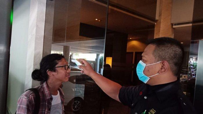 Salah satu pengunjung hotel di Batam sedang melakukan cek suhu tubuh dengan thermal scanner, Jumat (7/2/2020).