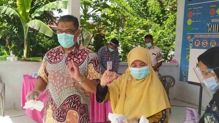 PILKADA KEPRI - Suryani bersama suami menggunakan hak pilihnya di Batam, Rabu (9/12/2020).