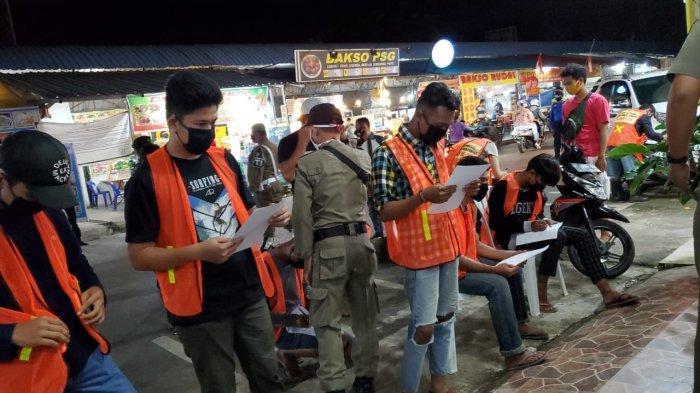 RAZIA MASKER - Pjs Wali Kota Batam, Syamsul Bahrum mengenakan masker kepada seorang warga yang tidak memakai masker, Sabtu, (03/10) malam.