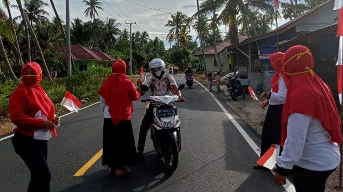 HUT RI - Polindes Kote Sakti, Kecamatan Singkep Pesisir Lingga bagikan bendera mini di jalan raya kepada para pengendara yang melintas saat HUT Ri ke-76, Rabu (18/8).