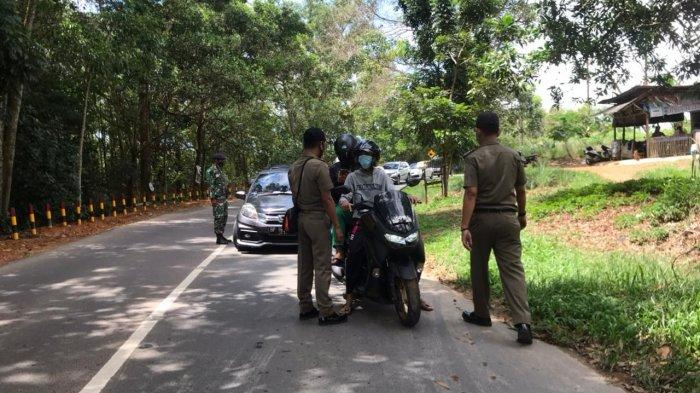 Pemberlakuan Pembatasan Kegiatan Masyarakat atau PPKM Darurat di Tanjungpinang. Tampak petugas berjaga di jalan perbatasan Kijang, Bintan - Tanjungpinang, tepatnya di Km 13 Daerah Sungai Pulai, Senin (12/7/2021).