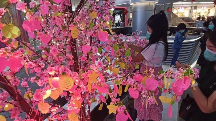 Promo Grand Batam Mall Sambut Imlek, Diskon Hingga 70 Persen untuk Fashion Hingga Makanan. Foto seorang pengunjung sedang memasang harapan ke wishing tree di Grand Batam Mall, Kamis (28/1/2021).