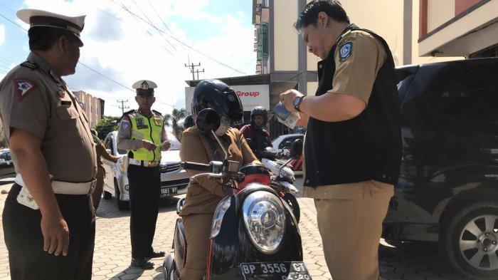 Petugas UPT PPD Kijang Samsat Kepri bersama Satlantas Polres Bintan memeriksa dokumen kendaraan bermotor yang melintas di KM 16, Toapaya, Bintan, Selasa (3/3/2020).