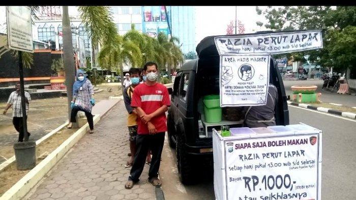 Warga mengantre untuk  mendapat makanan subsidi silang pahala razia perut lapar Bripka Zulhamsyah, di kawasan Pelabuhan Sri Bintan Pura Tanjungpinang, Jumat (19/2/2021).