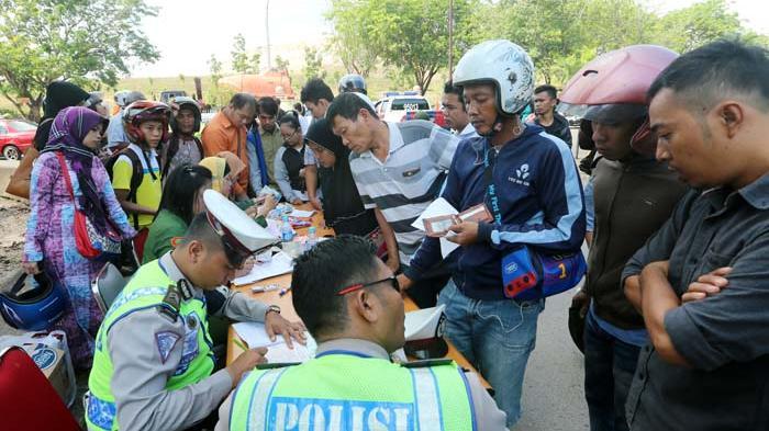 Seorang polisi saat memeriksa kelengkapan dokumen kepada salah satu pengendara dalam razia yang digelar di jalan Gajah Mada, Tiban Centre, Senin (13/4/2015).