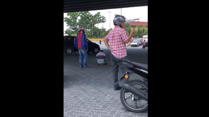 Tangkapan layar dari video orang salat di tengah jalan sampai dijaga para pengendara motor. Peristiwa ini terjadi di Malaysia pada Kamis (25/2/2021) dan viral di media sosial