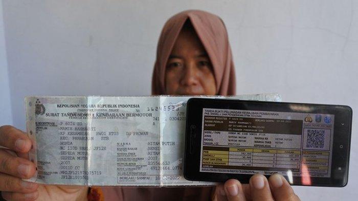Seorang warga memperlihatkan bukti pelunasan pajak kendaraan bermotor yang dibayar secara daring atau online dari rumah di Panarukan, Situbondo, Jawa Timur, Kamis (26/3/2020). Pembayaran secara online itu karena diliburkannya pembayaran secara langsung melalui Samsat untuk mencegah penularan Covid-19.