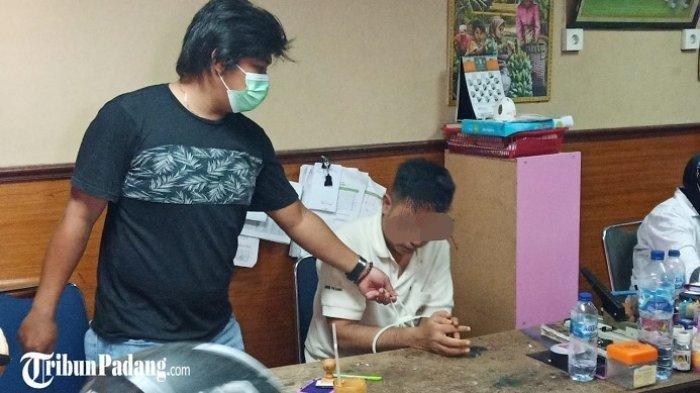 Seorang pecatan polisi saat diamankan Polresta Padang karena diduga melakukan KDRT.