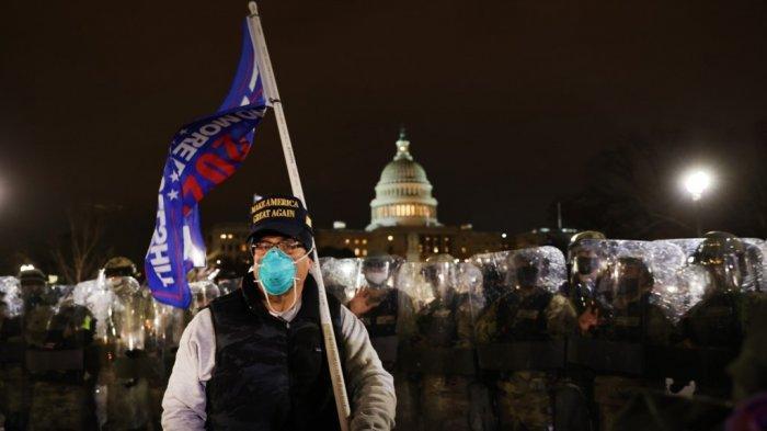 Seorang pendukung Donald Trump berdiri di depan aparat keamanan yang menjaga Gedung Capitol tempat anggota Kongres Amerika Serikat menggelar sesi untuk menyertifikat Presiden terpilih Joe Biden, Rabu (6/1/2021) malam atau Kamis pagi WIB.