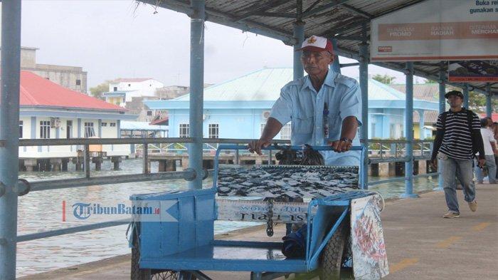 Suparmo sedang menyahuhkan becaknya di Pelabuhan Sri Bintan Pura