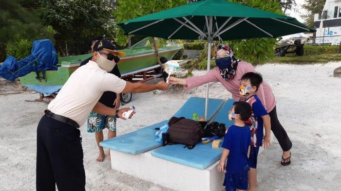 Staf Lagoi Bay memberikan suvenir Bintan Resort kepada pengunjung. Suvenir diberikan kepada pengunjung yang taat dalam menerapkan protokol kesehatan.