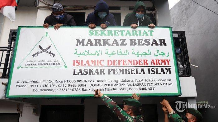 Pasukan TNI-polri berpakaian lengkap saat mencoba menurunkan atribut Front Pembela Islam (FPI) di kawasan Petamburan, Jakarta Pusat, Rabu (30/12/2020). Sebelumnya, Menko Polhukam Mahfud MD dalam jumpa pers yang didampingi sejumlah menteri dan kepala lembaga menyatakan bahwa Pemerintah melarang aktivitas FPI dan akan menghentikan setiap kegiatan FPI, karena FPI tidak lagi memiliki legal standing. keputusan tersebut tertuang dalam Surat Keputusan Bersama (SKB) 6 Pejabat Tertinggi. Mereka yang membubuhkan teken pada SK Bersama itu adalah Menteri Dalam Negeri, Menteri Hukum dan HAM, Menteri Komunikasi dan Informatika, Jaksa Agung, Kapolri, serta Kepala Badan Nasional Penanggulangan Terorisme (BNPT). Tribunnews/Jeprima