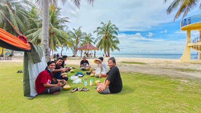 PULAU BENAN - Pengunjung menikmati air kelapa muda di area pantai wisata di Lingga, Pulau Benan, Kecamatan Katang Bidare, Kammis (17/6).