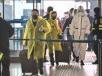 orang-orang-mengenakan-pakaian-pelindung-diri-melintas-di-bandara-tianhe.jpg