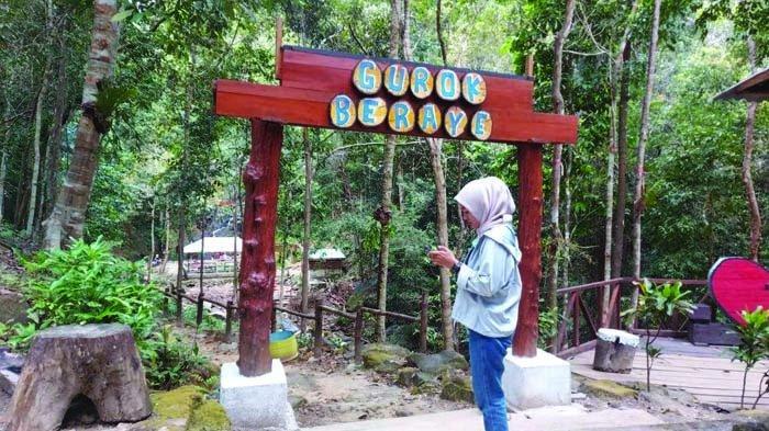 Pengunjung saat berada di gerbang kayu bertuliskan Gurok Beraye, Sabtu (6/3/2021).