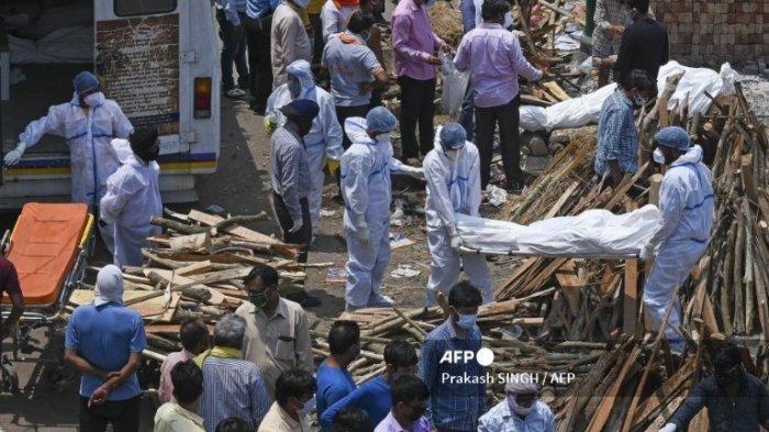 Anggota keluarga dan pekerja ambulans yang mengenakan APD membawa jenazah pasien yang meninggal karena Covid-19 di tempat kremasi di New Delhi pada 27 April 2021.