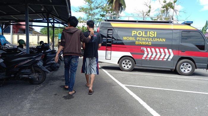MT (27) (baju hitam) saat dibawa oleh anggota Polres Belitung untuk dimintai keterangan, Jumat (25/6/2021)