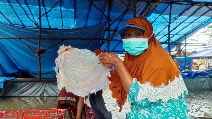 Dahara bersama rekannya sesama buruh saat sibuk membersihkan ubur-ubur di tempat pengemasan di Dusun Teluk Dalam, Desa Juru Seberang, Rabu (14/7/2021).