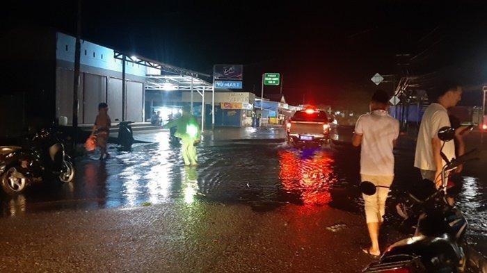 Satu unit mobil melintasi genangan air di ujung Pasar tradisional Kelapa kampit, curah hujan menyebabkan air tergenang selutut orang dewasa. Minggu (17/1/2021)