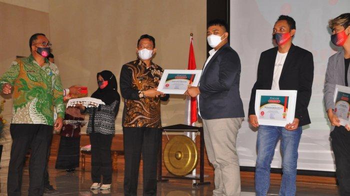 PENYERAHAN PENGHARGAAN - Bupati Belitung Timur menyerahkan penghargaan kepada pimpinan Indigo Grup pada momen peluncuran Lawang Beltim di Auditorium Zahari MZ, Manggar, Kamis (10/6). (IST/DOK DISKOMINFO BELTIM)