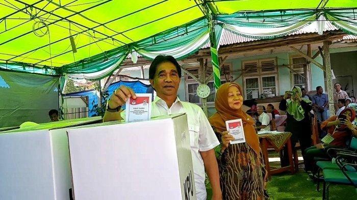 Bupati Beltim Yuslih Ihza Pakai Kemeja Putih Ajak Istri Nyoblos di TPS 11 Dusun Samak