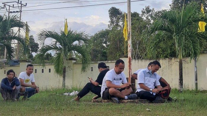 Burhanudin calon Bupati Belitung Timur, duduk dibawah tiang bendera sambil menunggu penghitungan cepat dari tim Berakar.