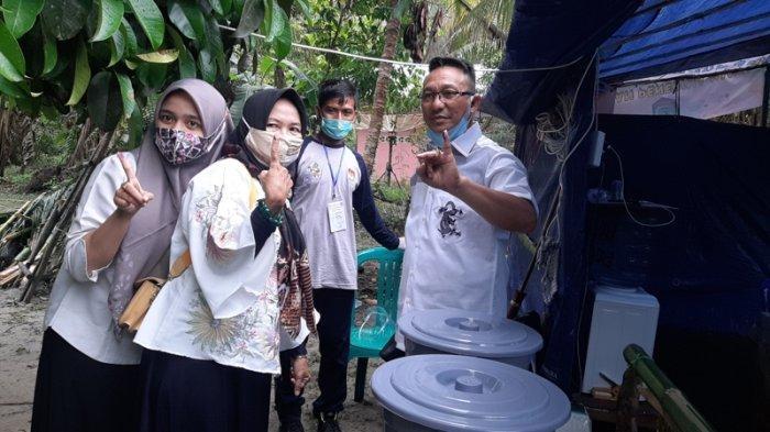 Burhanudin bersama istri dan anaknya saat melakukan pencoblosan di TPS 4 Desa mayang Kecamatan Kelapa Kampit, Belitung Timur. Rabu (9/12/2020).