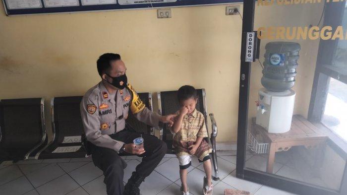 Gilang bocah usai empat tahun yang tersesat di jalan diantar warga ke Kantor Polsek Gerunggang. Seorang anggota polisi menenangkannya dan menanyakan alamat rumahnya agar bisa diantar pulang.
