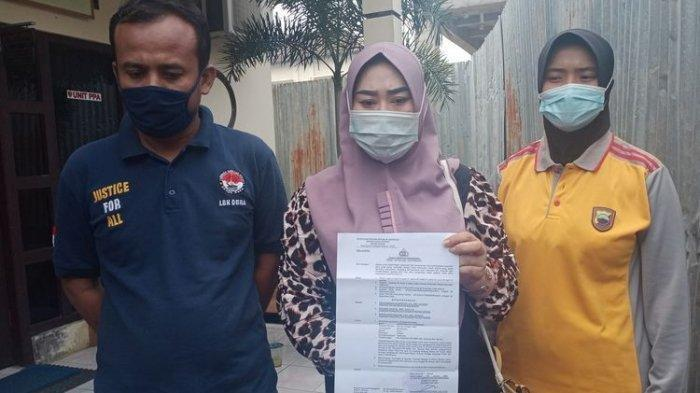 Seorang ibu berinisial S (36) didampingi kuasa hukumnya Haryanto menunjukan surat penahanan atas laporan anak kandungnya sendiri di Polres Demak Jawa Tengah, Jumat (8/1/2021).