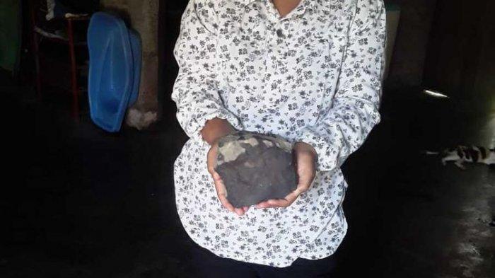 Isteri Josua Hutagalung (33) warga Dusun Sitahan Barat, Desa Satahi Nauli, Kecamatan Kolang, Kabupaten Tapanuli Tengah menunjukkan batu yang diduganya sebagai meteor setelah jatuh menimpa rumahnya, Sabtu (1/8/2020).